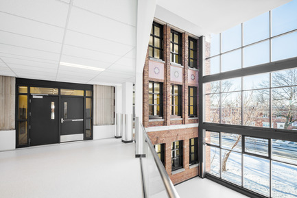 Press kit | 752-03 - Press release | Bronze tightrope walker… welcomes Park Extension schoolchildren - NFOE et associés architectes - Institutional Architecture - Full-height glazed atrium highlights one of the older brick facades - Photo credit: Charles Lanteigne