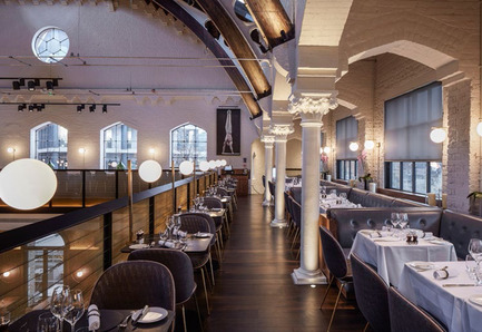 Press kit | 1124-09 - Press release | WIN Awards - Hospitality Shortlist Announced - World Interiors News - Commercial Interior Design - WIN Awards 2016 - Restaurants Category: The German Gymnasium by Conran & Partners (United Kingdom) <br><br>Conran & Partners were commissioned to create a glamorous yet democratic contemporary European Grand Café, Bar and Restaurant to complement the newly invigorated King's Cross master plan, and transform the Grade II-listed building into a unique destination. Our concept is a refined modern insertion within the existing building; a Bauhaus version of a European Grand Café.<br><br>'The ground floor dining area, suffused with natural light which captures the building's delicate silhouettes of cast steel columns and Victorian archways, makes an immediate impact. Two new contemporary black steel staircases symmetrically frame the space, adding drama and elegance.<br><br>Everyone was incredibly impressed by the opportunity of the existing building, at the same time understanding the challenges of the existing elements. The gallery, which has been exposed, is very restrained. On paper it shouldn't work because it is only one table deep, but it does work as a proper gallery and vantage point. The composition of the seating creates very nice zones and the restrained palette is sympathetic to the existing building. A well-received project.' JD<br> - Photo credit: Conran & Partners