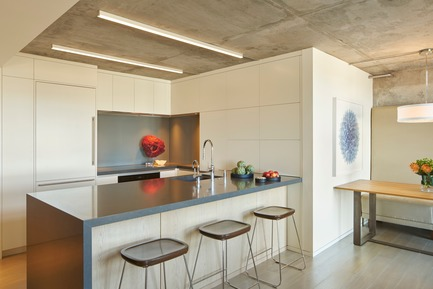 Press kit | 1733-03 - Press release | SOMA Loft Residence - Studio VARA - Residential Interior Design - The kitchen, a compact composition of white lacquer casework opens to harbor views over an oversized island - Photo credit: Bruce Damonte