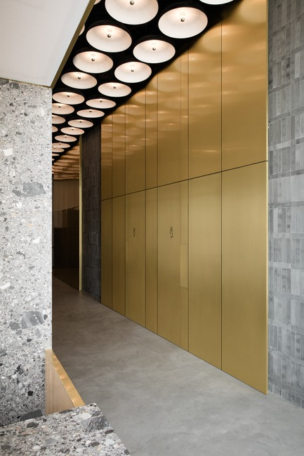 Press kit | 3809-01 - Press release | Warehouse GYM D3 - VSHD Design - Commercial Interior Design - The main corridor cladded in gold copper alloy leading to the male and female changing rooms with concealed doors of the same material. - Photo credit: Nik and Tam