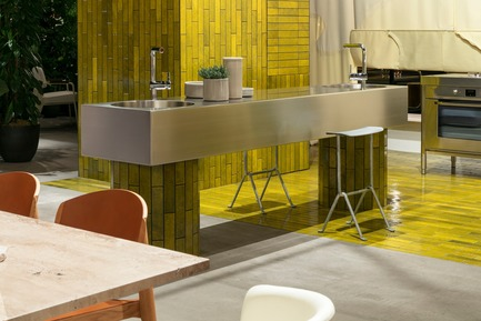 "Press kit | 2704-05 - Press release | ""Das Haus"" 2019 at the imm cologne: Living by moods creates an appetite for open-plan homes - imm cologne 2019, Koelnmesse GmbH - Residential Interior Design - The kitchen is the centre of Studio Truly Truly's installation at imm cologne 2019. Its islands extend into the living area.The designers' aim was to slow the pace of kitchen workflows.The cooking module (Alpes Inox) is accompanied among other things by a stainless steel sink block (a prototype by Studio Truly Truly). - Photo credit: Constantin Meyer; Koelnmesse"